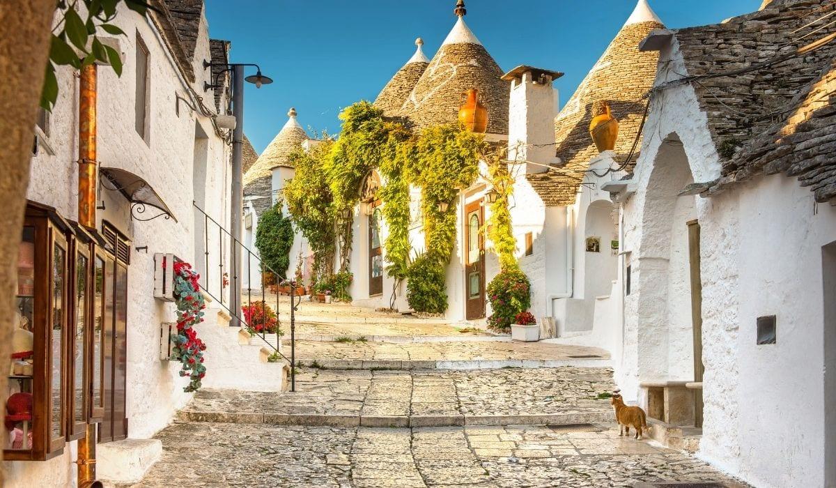 Trulli line a sun-lit street in Alberobello, Italy, oneo f the most beautiful European towns.