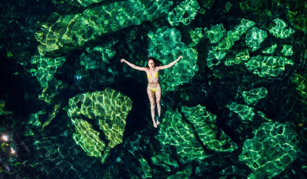 Woman floating in Cenote Cristalino in Riviera Maya, Mexico.