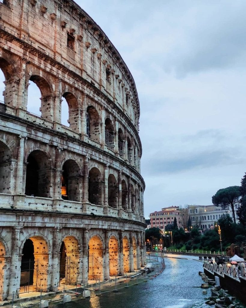 Colosseum in Rome, set against a pale grey sky littered with clouds, wet pavement on a rainy day.