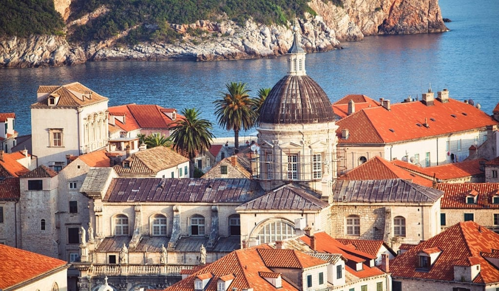 Croatia's stunning capital city, Dubrovnik with sea views, palm trees, and red rooftops.