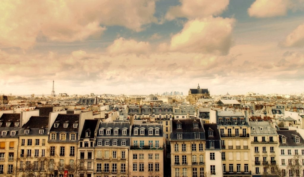 Overlooking the roofs of Paris with the Eiffel Tower in the far background, cloudy and hazy skies.
