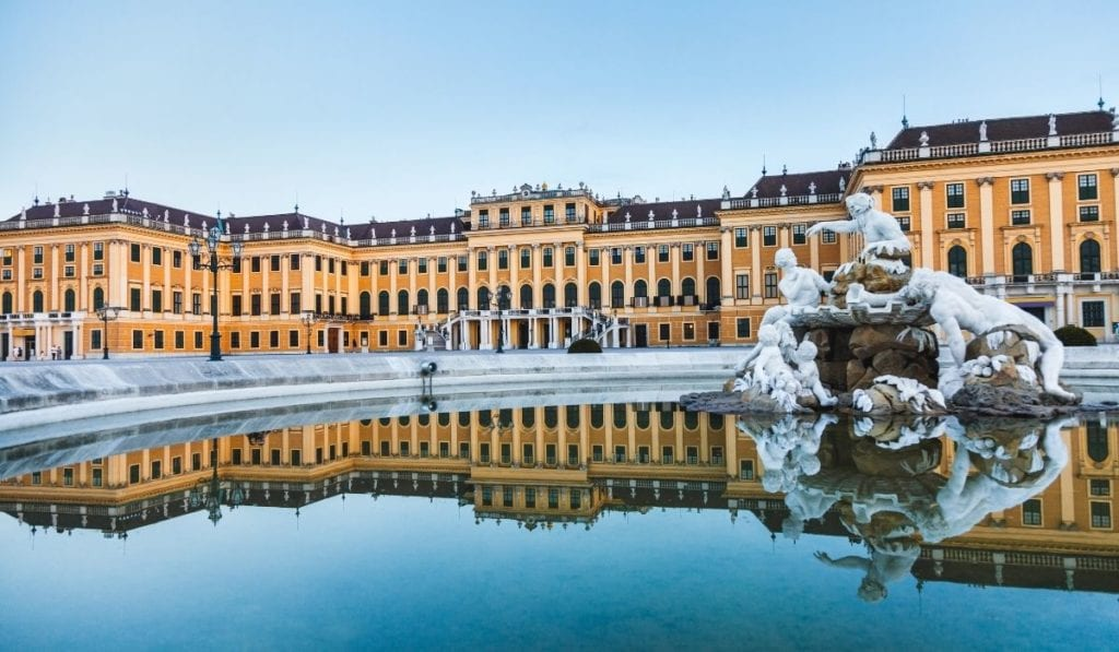 Schonbrunn Palace in Vienna, reflected in the water of the fountain in front.