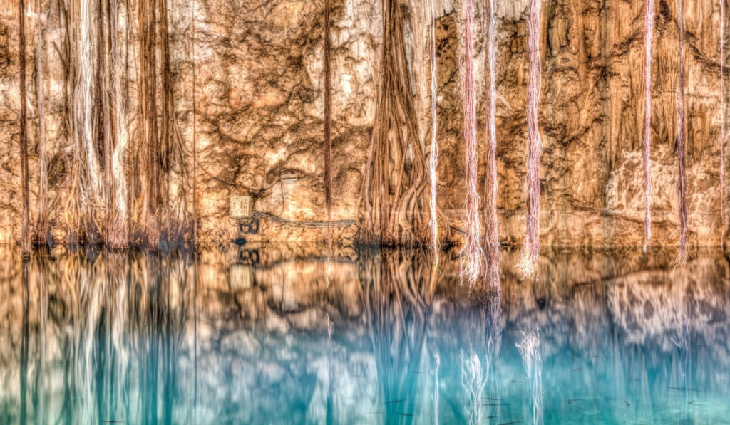 Beautiful cavernous wall of stalagmites and stalactites dipping into the teal waters of Cenote Xkenken.