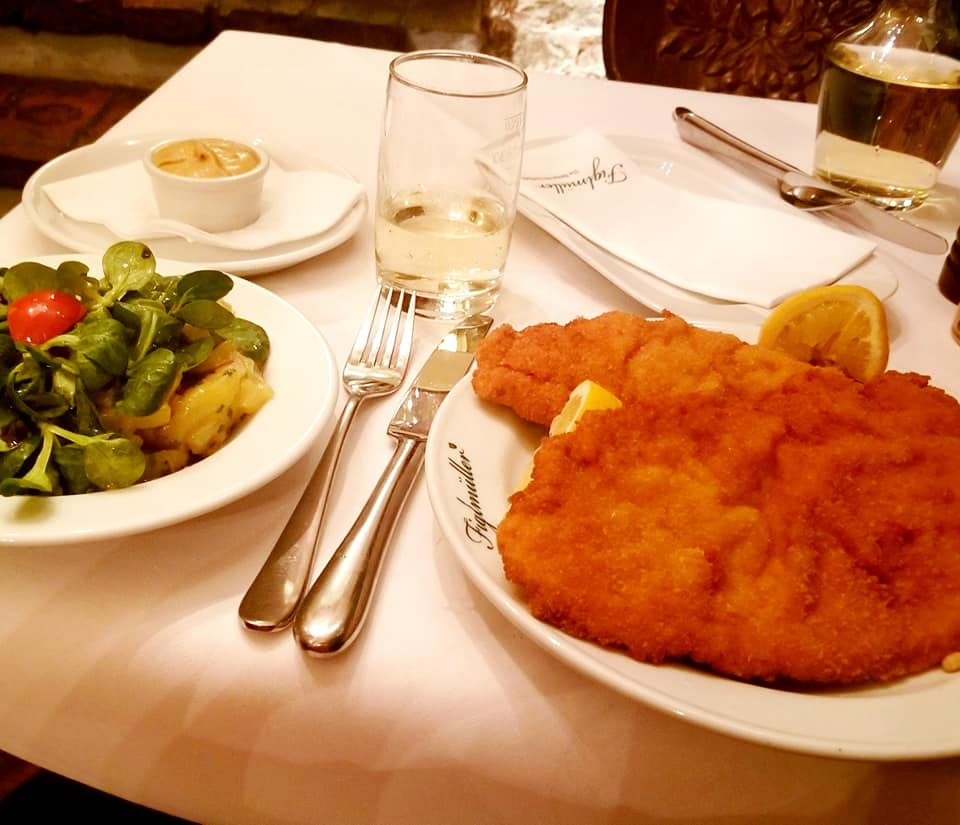 Famous Wiener Schnitzel at Figlmuller restaurant in Vienna, Austria.  The schnitzel is so big, the edges are not on the plate.  It is served with cut lemon wedges.  There is a potato salad with dressed field greens and tomato next to the plate of schnitzel.  It is a white-linen restaurant with fine silverware and servers wearing suits.