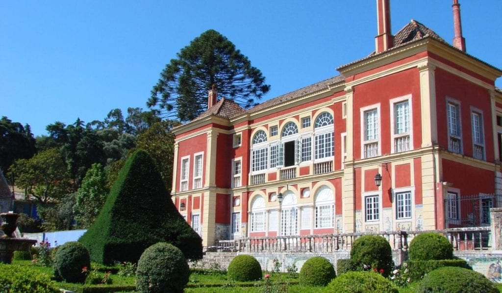 Red building with manicured gardens at the Palacio Fronteira in Lisbon.