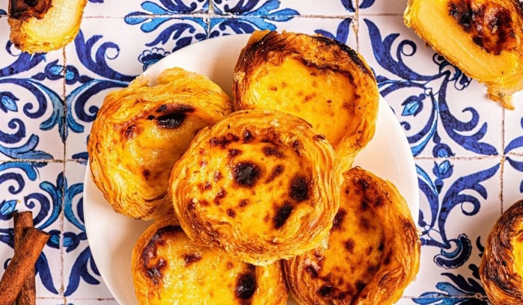 Heaping plate of pasteis de nata, a traditional Portuguese breakfast treat on an azulejo tile table.