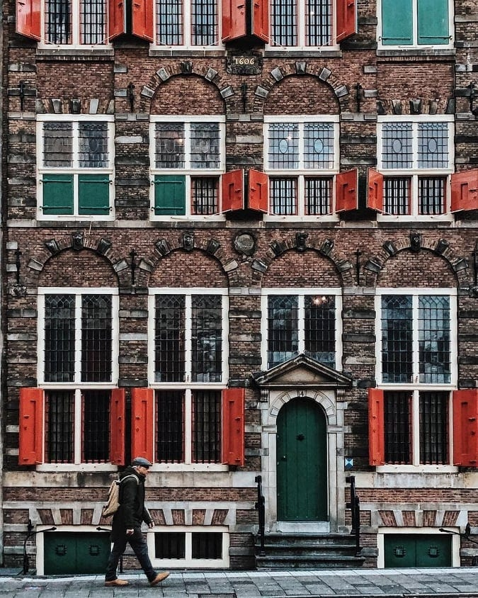 Man walking by the iconic Rembrandthuis in Amsterdam with the green door and red shutters.