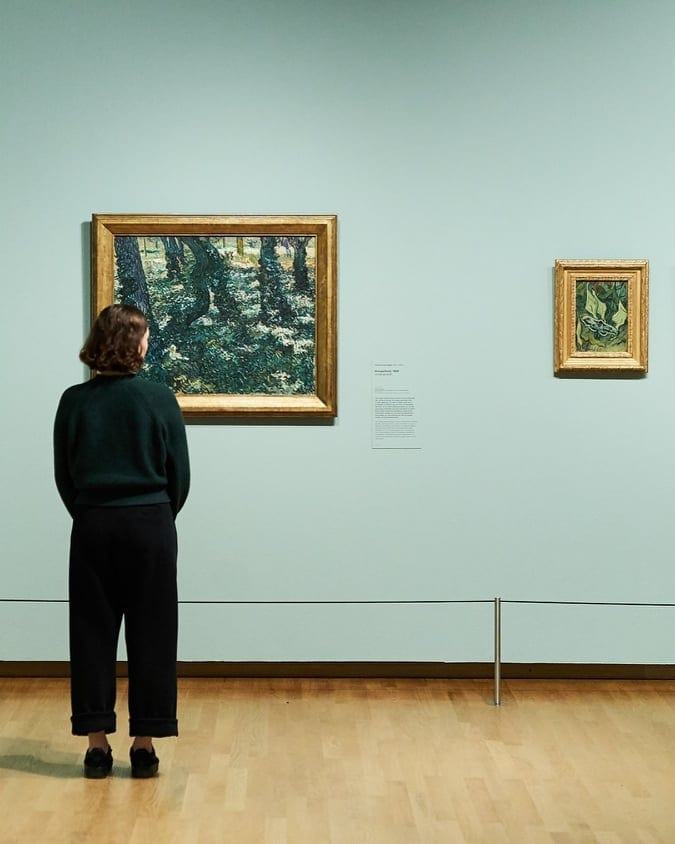 Woman looking at paintings at the Van Gogh Museum in Amsterdam, the Netherlands.