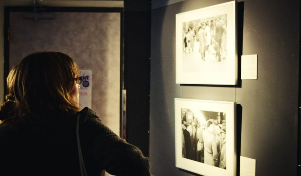 Woman looking at photo exhibition in the Dutch Resistance Museum in Amsterdam.