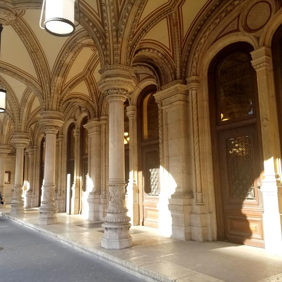 Ornate columns outside of the Vienna State Opera house with light and shadow play from the position of the sun.