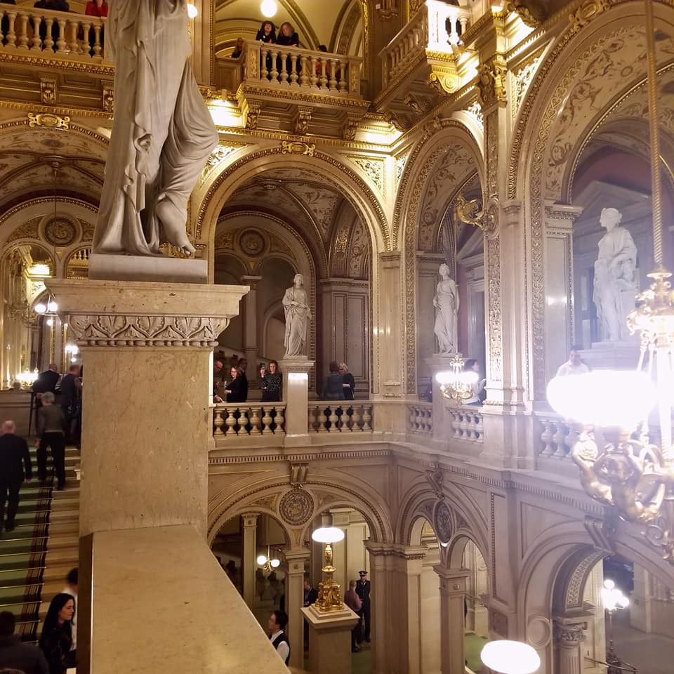 Interior of the Vienna State Opera overlooking the floors below.  From this view, the chandelier is at eye-level.  In each of the arches is a statue of different women.  There are many opera go-ers walking around during the intermission.