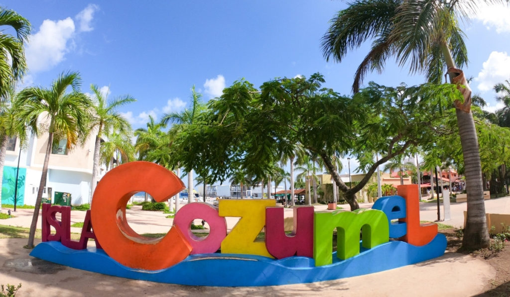 Brightly colored 'Isla Cozumel' sign on the beach with colorful hammocks shown.