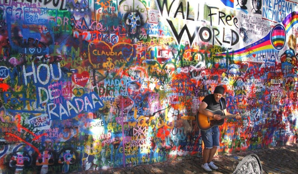 Man playing acoustic guitar in front of the John Lennon wall in Prague, one of the city's hidden gems.