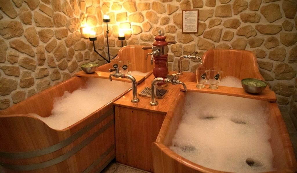 Two wooden tubs with a beer tap in the middle, filled with suds - one of Prague's beer spas.