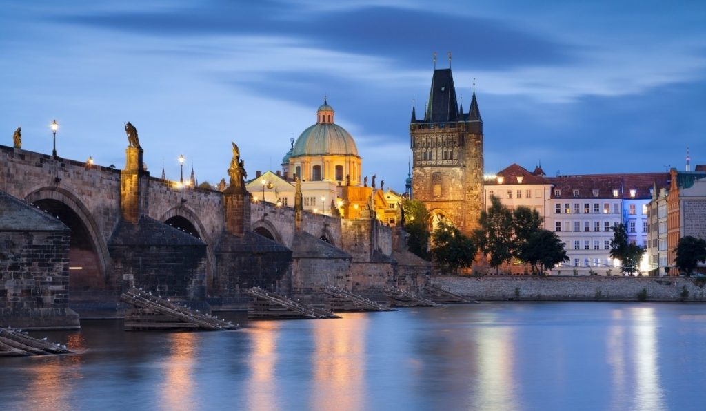 Prague bridge over river at dusk with the lights reflecting on the river.