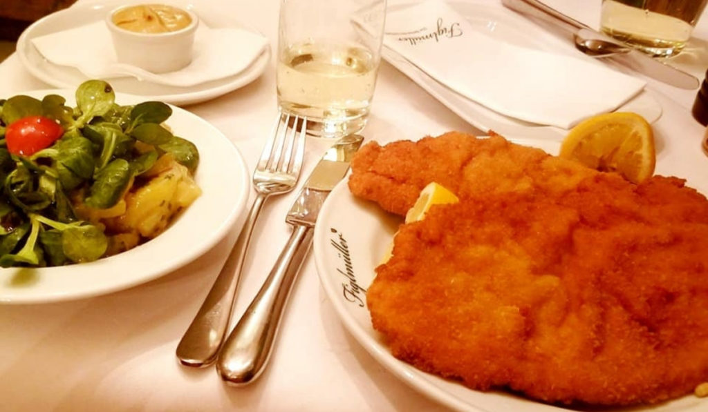 Large plate of schnitzel and potato salad at a restaurant in Vienna.