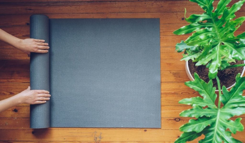 Hands rolling up a yoga mat next to large green, leafy plants.