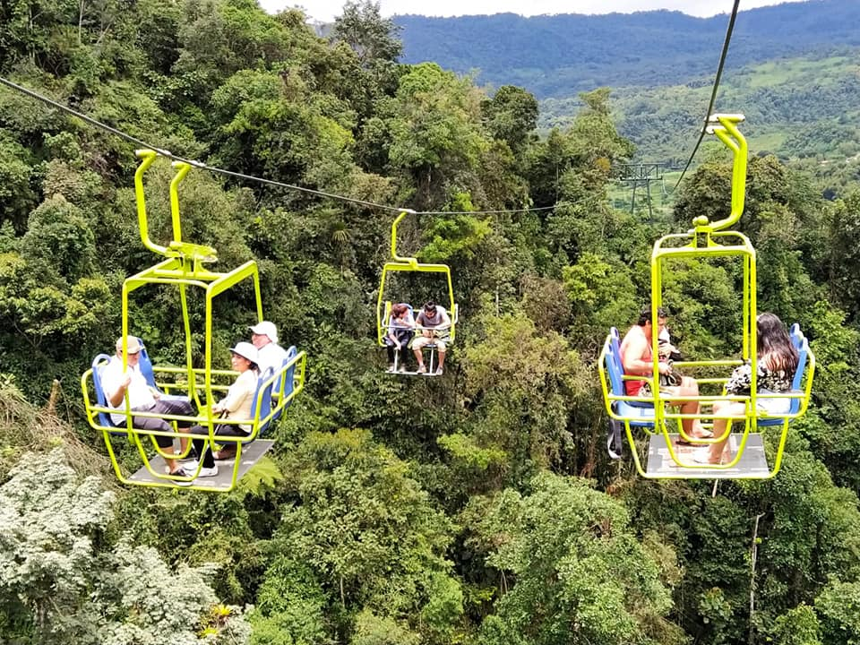 Minjoy Park Chairlift showing three different lifts with groups of people above the canopy in the Mindo Cloud forest.